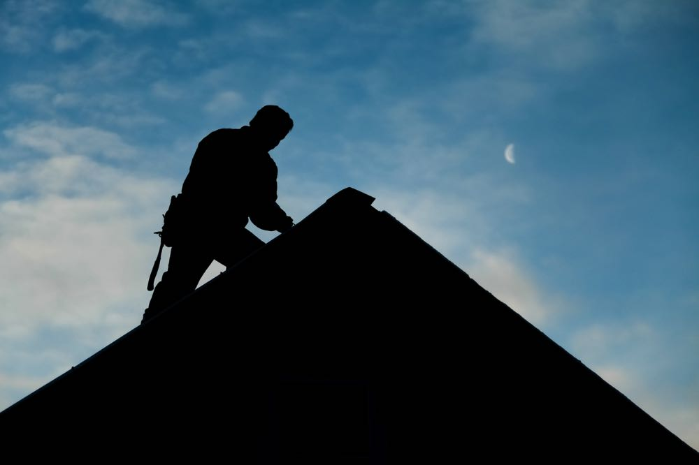 contractor in silhouette working on a roof top PFBKLZ8